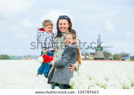 Mother with her child walks between of the white tulips field