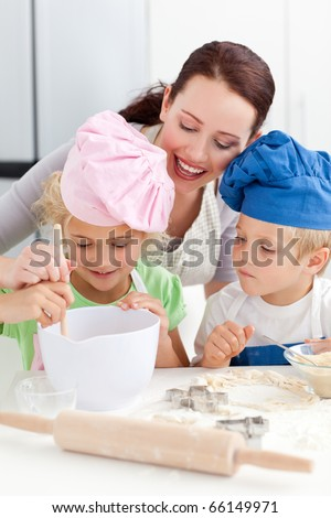 Mother with her children baking together in the kitchen to make cookies