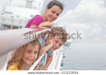 Mother with her children stand on deck of large passenger ship near handrails, focus on girl - stock photo
