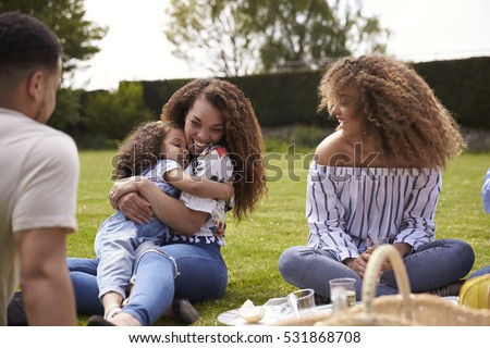 Mother with her daughter and adult friends at a picnic