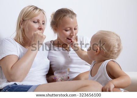 Mother with her daughter and son sitting on the sofa, eating candy and laughing - stock photo