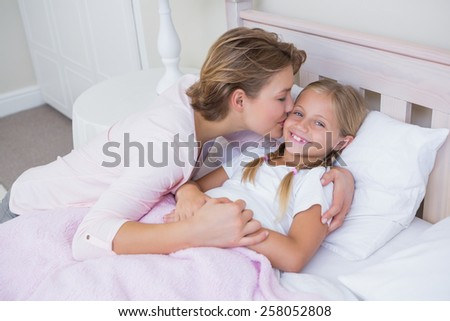 Mother with her daughter at bedtime at home in the bedroom - stock photo