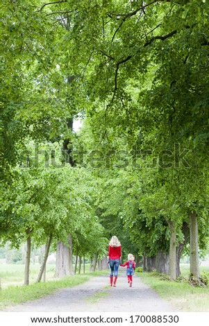 mother with her daughter in spring alley - stock photo