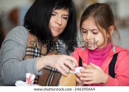 Mother with her daughter making rag Ukrainian national doll (motanka) - stock photo