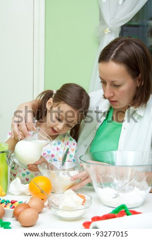 mother with her daughter prepearing in kitchen - stock photo