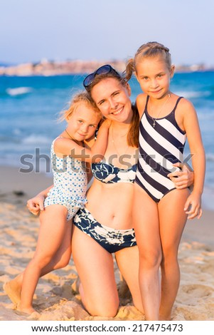 Mother with her daughters at the seashore, happy family concept