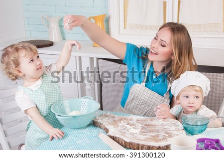 Mother with her daughters in the kitchen, preparing dinner, happy family - stock photo