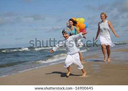 Mother with her daughters on the beach - stock photo