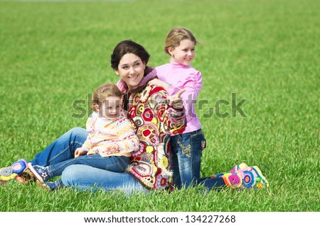 Mother with her daughters on the green field - stock photo