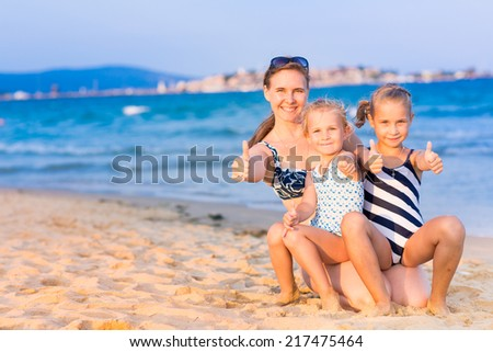 Mother with her daughters with thumbs up at the seashore, happy family concept