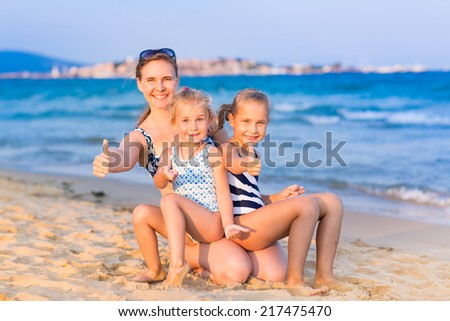 Mother with her daughters with thumbs up at the seashore, happy family concept - stock photo