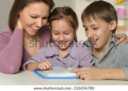 Mother with her kids doing homework at home - stock photo