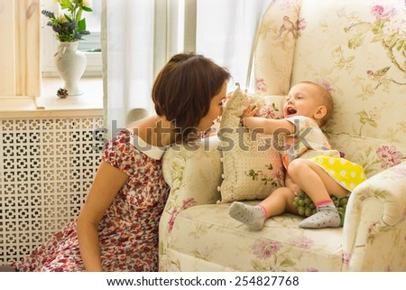 Mother with her little daughter are playing and grimacing with each other - stock photo
