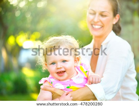 Mother with her little daughter having fun outdoors. Mom and her child little girl playing, enjoying nature together. Happy family