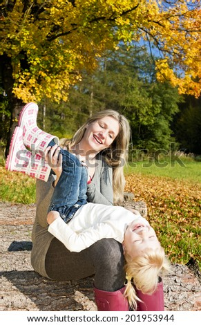 mother with her little daughter in autumnal nature - stock photo