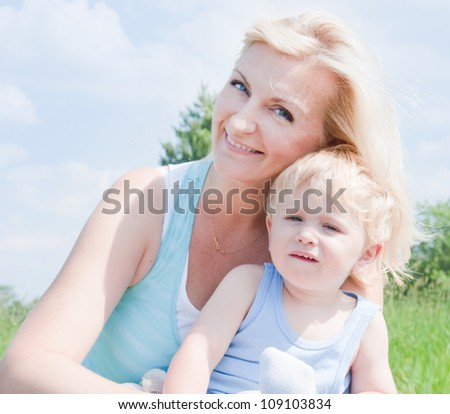 Mother with her little son in summer meadow