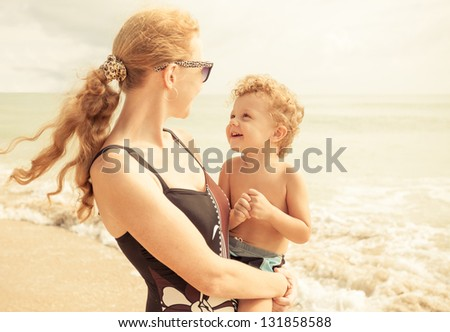 Mother with her little son on the beach - stock photo
