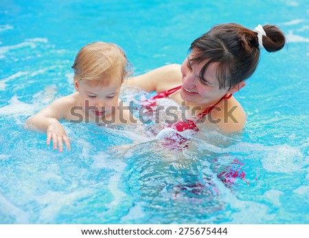 Mother with her lovely child in swimming-pool - stock photo