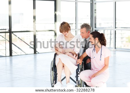 Mother with her newborn baby and doctors in hospital with copy-space - stock photo