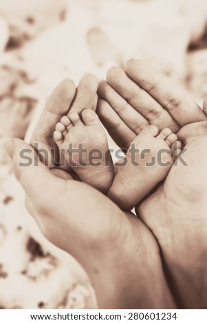 Mother with her newborn baby care hands black and white - stock photo