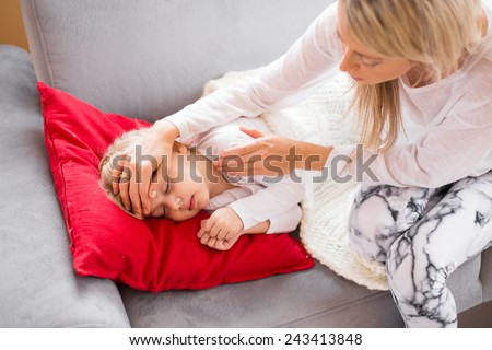 Mother with her sick kid at home - stock photo