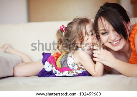 Mother with her small daughter playing on the sofa at home - stock photo
