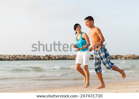 Mother with her son are running on the beach and having fun