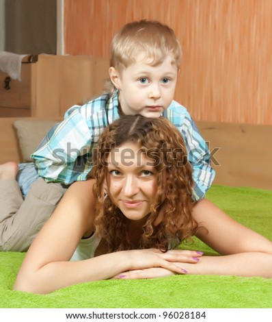 mother with her son in home interior - stock photo