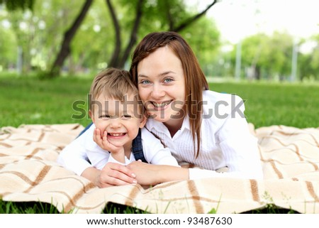 Mother with her son laying on the ground in the summer park - stock photo