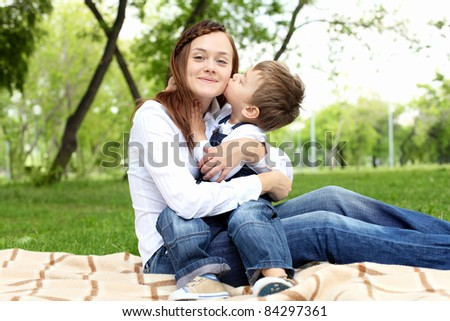 Mother with her son sitting and embracing in the summer park - stock photo