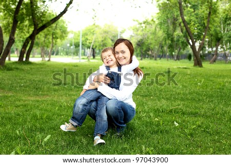 Mother with her son sitting on the grass  in the summer park - stock photo