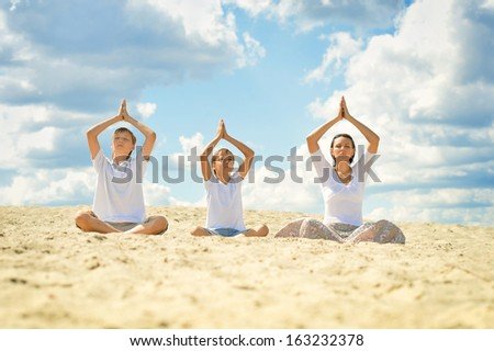 Mother with her sons sitting on a sand and doing yoga - stock photo
