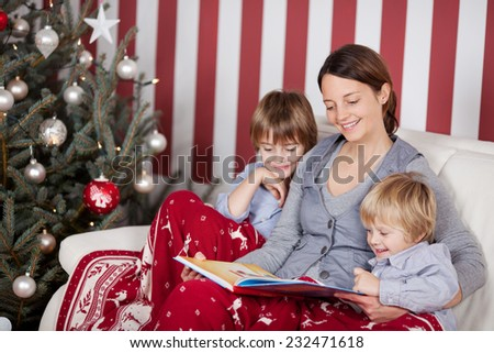 Mother with her two children at Christmas sitting on a sofa alongside the Christmas tree reading a book, red and white striped decor - stock photo