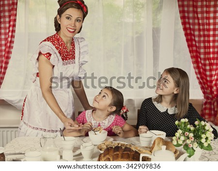 Mother with her two daughters have breakfast at home. Monochrome, grunge textures, intentional styled to the 1950s