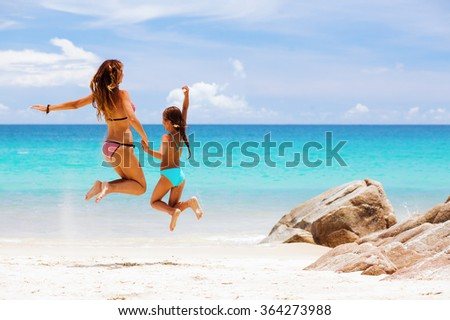 Mother with her 8 years old daughter resting on a tropical beach during summer vacations