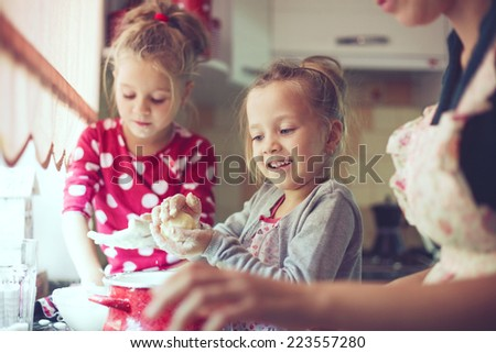 Mother with her 5 years old kids cooking holiday pie in the kitchen, casual lifestyle photo series in real life interior - stock photo