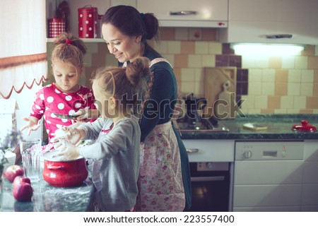 Mother with her 5 years old kids cooking holiday pie in the kitchen to Mothers day, casual lifestyle photo series in real life interior - stock photo