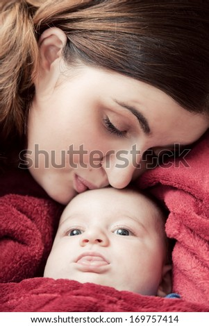 Mother with her young baby cuddling and kissing him on forehead. Parenthood, love.