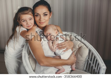 mother with infant boy and child girl having fun at home. woman with two children. Young mother playing with her little baby on the bed - indoors. Portrait of mother with two daughters in white room - stock photo