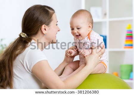 Mother with kid doing exercises with green gymnastic ball at home. Concept of caring for the baby's health. - stock photo