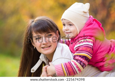 mother with kid girl outdoor in fall - stock photo