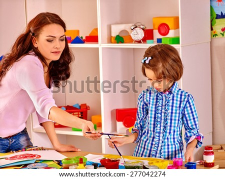 Mother with kid  painting  child picture in school. Education. - stock photo