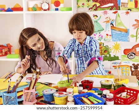 Mother with kid  painting  in school. Education. - stock photo