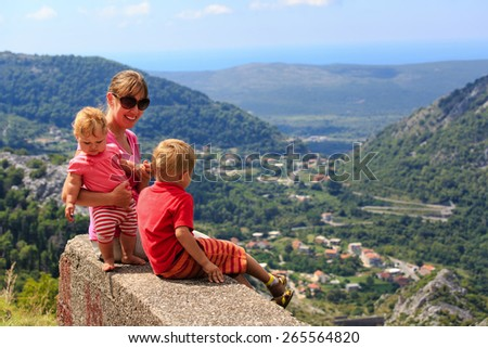 mother with kids having rest in summer mountains - stock photo