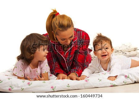 Mother with kids in bed having fun together - stock photo