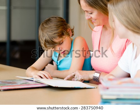 Mother with kids in library with books - stock photo