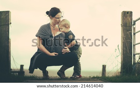 mother with kids kissing  - stock photo