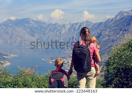 mother with kids looking at mountains on summer vacation