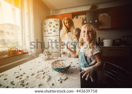 Mother with kids on kitchen play with flour - stock photo