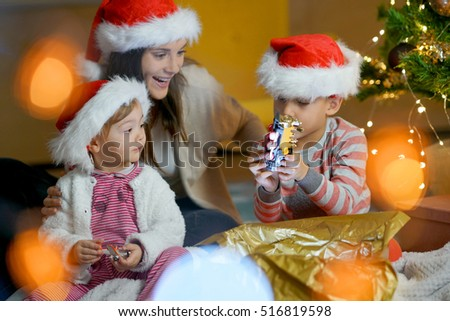 Mother with kids opening Christmas gifts